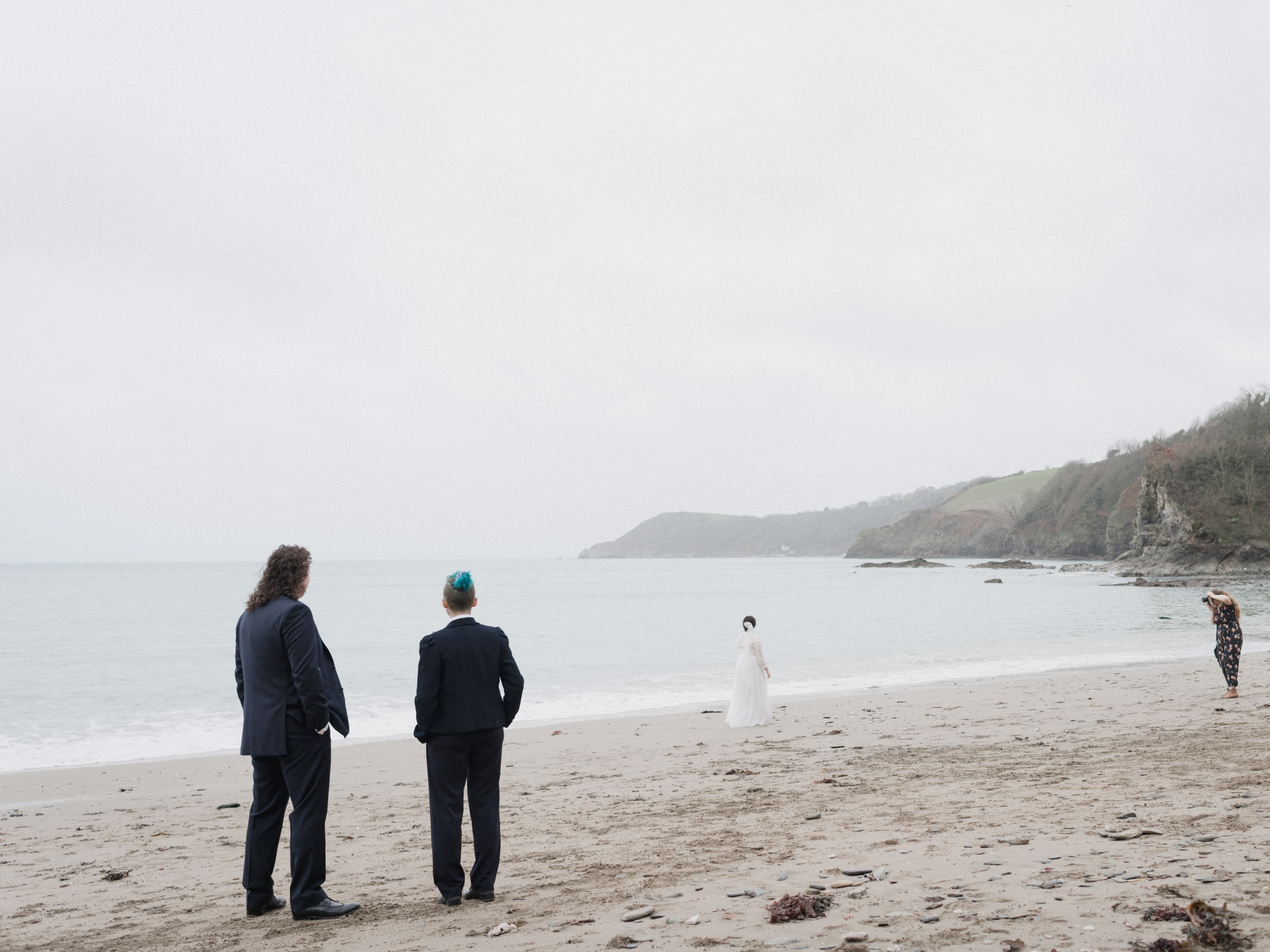 On a sandy beach by the sea, two people in suits watch a bride in a white dress being photographed in the distance