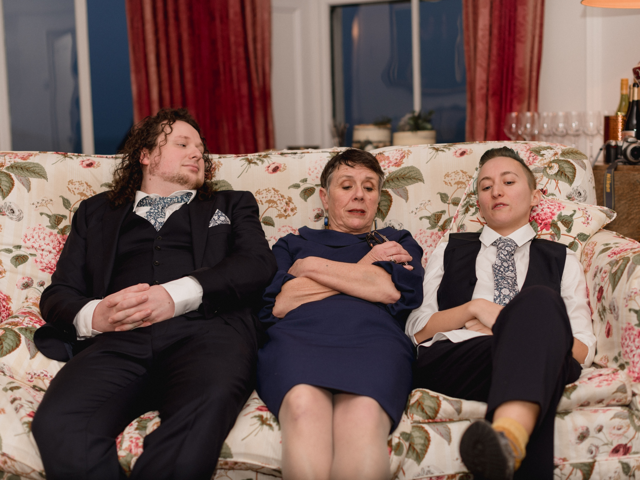 Three people slouch on a floral couch; one in a navy suit, one in a navy dress, and one in a white shirt and navy waistcoat