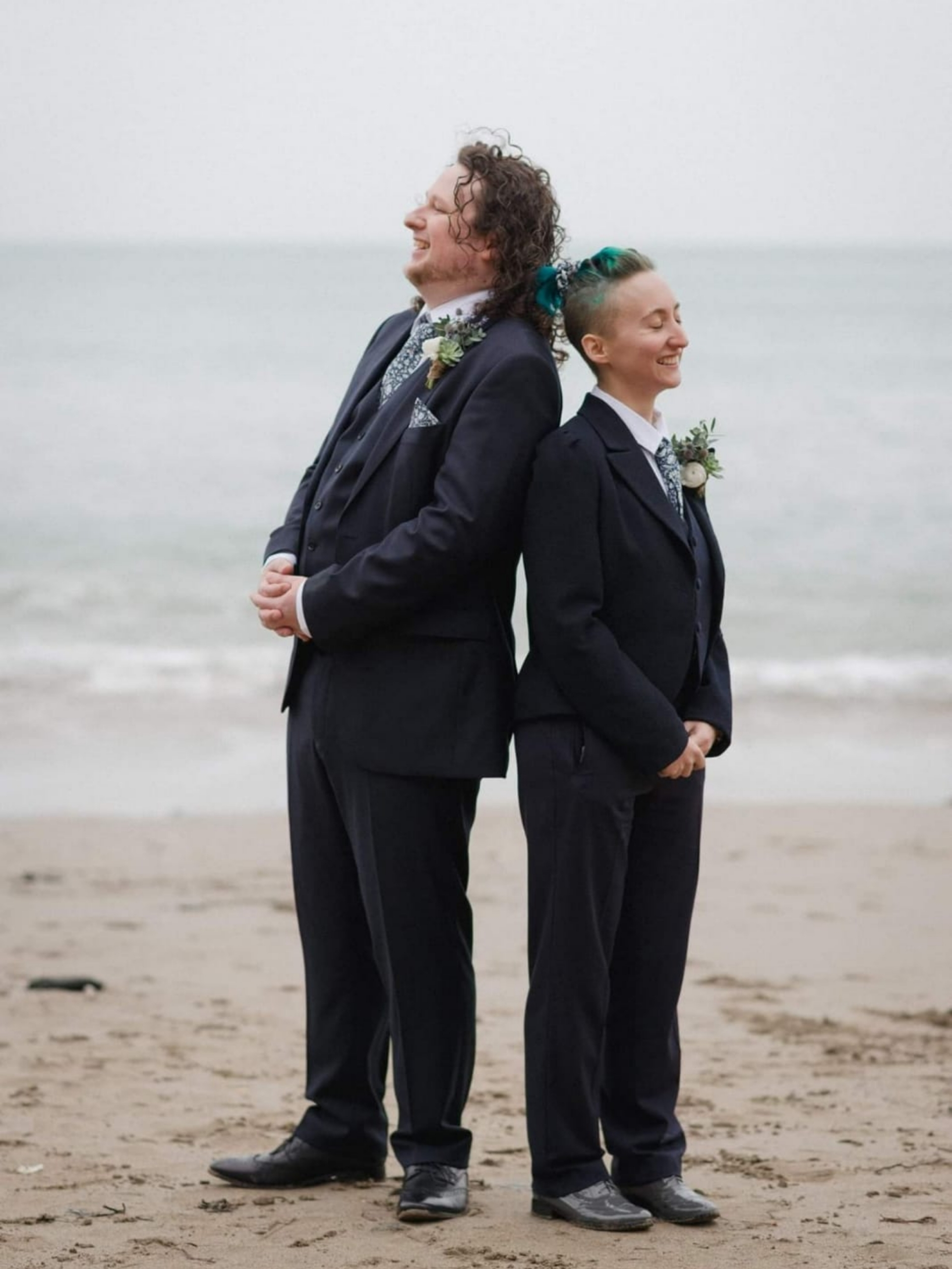 Two people in navy suits stand back to back on the beach, laughing